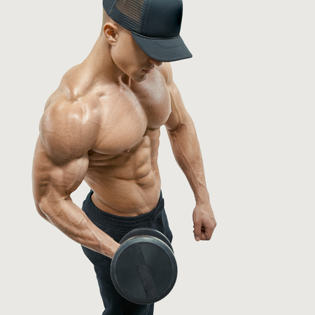 calisthenics: Closeup of a handsome power athletic man bodybuilder lifting heavy dumbbells. Handsome power shirtless man in training pumping up muscles with dumbbell. Wearing a  baseball cap. Vector clipping mask