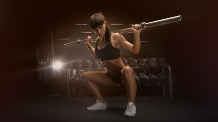 Sport, bodybuilding, lifestyle concept Fit young woman in great shape lifting barbells looking down, working out in a gym Sporty sexy woman doing squat workout Strong legs