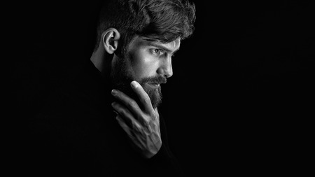 man profile: Black and white image of attractive pensive young man looks into the distance stroking his beard over black background Stock Photo