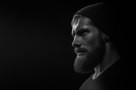 Silhouet van jonge bebaarde man hipster dragen zwarte gebreide muts. Zwart-witte studio die op donkere achtergrond is ontsproten