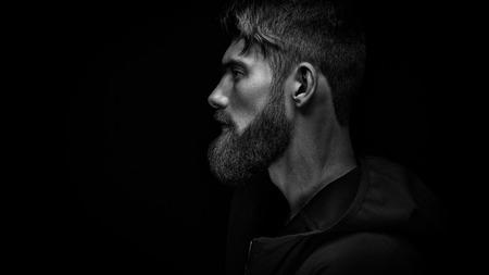 Immagine in bianco e nero di singolo standing di profilo giovane bello serio uomo barbuto in cappuccio nero su sfondo nero con copia spazio. Archivio Fotografico - 70536225
