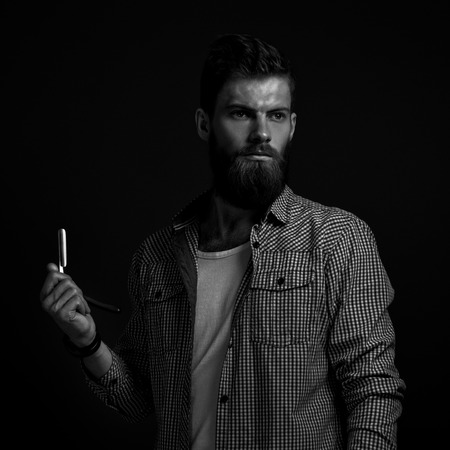 male fashion model: Black and white portrait of brutal bearded man with straight razor Stock Photo