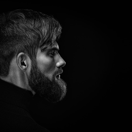 Black and white close up image of serious brutal bearded man on dark background Confident and dramatic concept