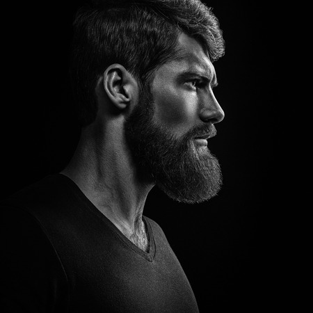 Dramatic concept Black and white close-up portrait of young handsome bearded man looking forward. Studio shot on black background 스톡 콘텐츠