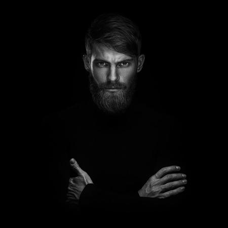 Zwart en wit portret van serieuze jonge man met gevouwen en kruising handen staan ??geïsoleerd op zwarte achtergrond en kijken naar camera Vertrouwen concept