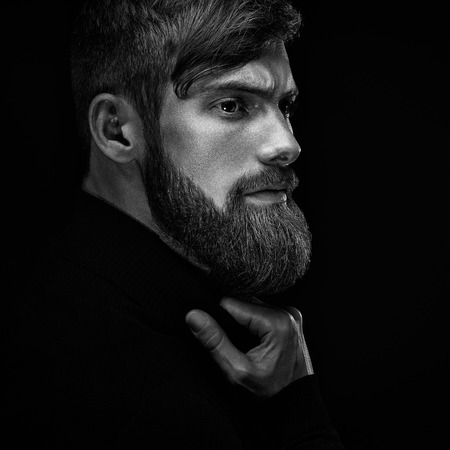 Black and white portrait of young bearded man isolated at black background Guy with beard thoughtful, pensive, charming, looking forward Trendy hipster think of problem solving, finding solution