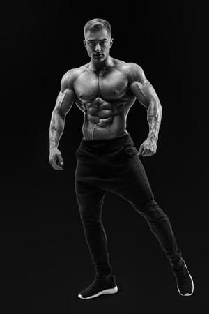 Black and white portrait of young athletic man with muscular physique. Shirtless male model standing confidently. Perfect fit, six pack, abs, abdominal muscle, shoulders, deltoids, biceps. Stock Photo