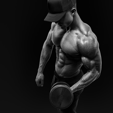 Black and white shot of a handsome power athletic man bodybuilder lifting heavy dumbbells. Handsome power shirtless man in training pumping up muscles with dumbbell. Wearing a baseball cap