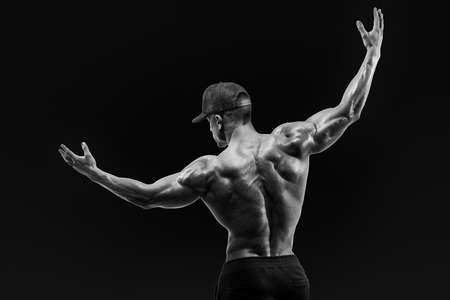 deltoids: Black and white shot of healthy muscular young man turning back and rise both hands. Perfect fit, six pack, abs, abdominal muscle, shoulders, deltoids, biceps. Stock Photo