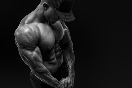 deltoids: Black and white shot of shirtless male bodybuilder with muscular build strong abs showing. Perfect fit, six pack, shoulders, deltoids, biceps. Bodybuilder in black cap muscular physique looking down Stock Photo