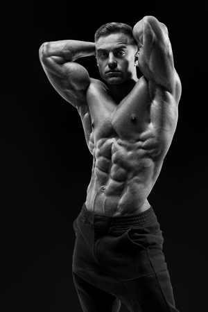 Black and white shot of shirtless male bodybuilder with muscular build strong abs showing. Healthy muscular young man. Perfect fit, six pack, abs, abdominal muscle, shoulders biceps triceps and chest.