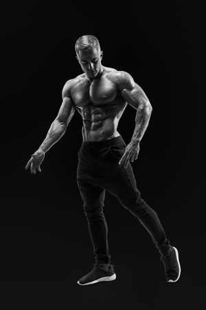 Full-length black and white shot of handsome young man with muscular body standing. Perfect fit, six pack, abs, abdominal muscle, shoulders, deltoids, biceps. Stock Photo