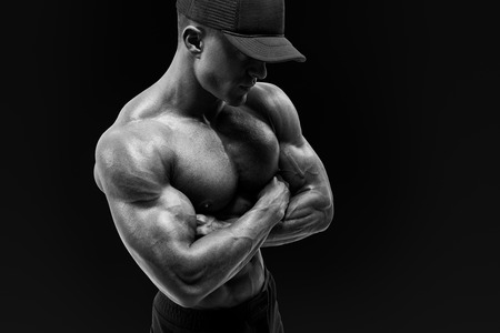 Black and white shot of healthy muscular young man with black baseball cap. Shirtless male bodybuilder with muscular build strong abs showing cross hands.