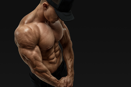 Shirtless male bodybuilder with muscular build strong abs showing. Perfect fit, six pack, abs, abdominal muscle, shoulders, deltoids, biceps. Bodybuilder in black cap with muscular physique looking down. Vector clipping mask path