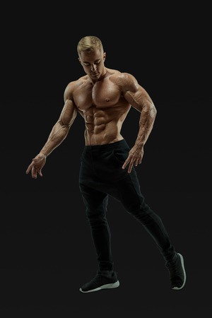 Full-length shot of handsome young man with muscular body standing against black background. Perfect fit, six pack, abs, abdominal muscle, shoulders, deltoids, biceps. Vector mask clipping path