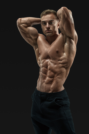 Shirtless male bodybuilder with muscular build strong abs showing. Shot of healthy muscular young man. Perfect fit, six pack, abs, abdominal muscle, shoulders, deltoids, biceps, triceps and chest. Banque d'images