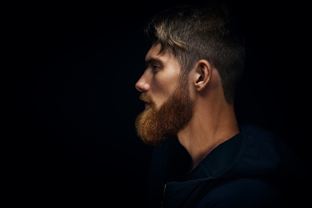 Close-up image of serious brutal bearded man on dark background Confident and dramatic concept Stock Photo