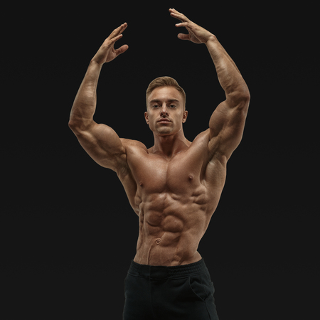 deltoids: Shot of healthy muscular young man. Perfect fit, six pack, abs, abdominal muscle, shoulders, deltoids, biceps. Shirtless male bodybuilder with muscular build strong abs showing rising hand.