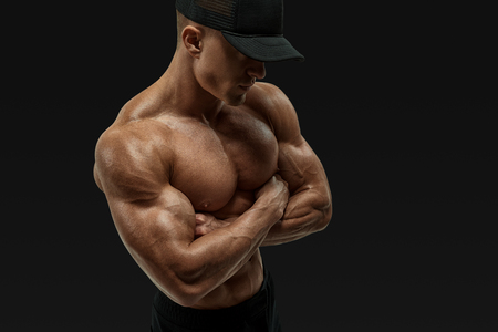 Shot of healthy muscular young man with black baseball cap. Perfect fit, six pack, abs, abdominal muscle, shoulders, deltoids, biceps. Shirtless male bodybuilder with muscular build strong abs showing cross hands.