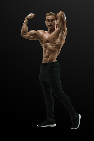 Body builder with muscular physique looking forward. Masculine young fitness male model posing shirtless against black background. Bodybuilder with muscular physique looking at camera showing biceps