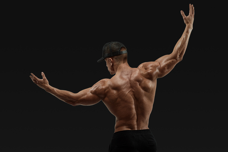 Shot of healthy muscular young man turning back and rise both hands. Perfect fit, six pack, abs, abdominal muscle, shoulders, deltoids, biceps. Vector path clipping mask