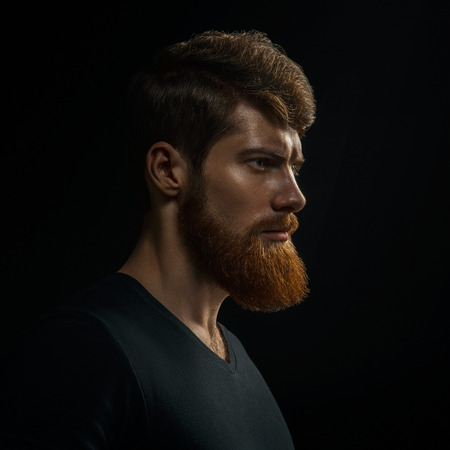 Studio shot of confidence attractive hipster Dramatic light concept Black background Copy space Bearded man