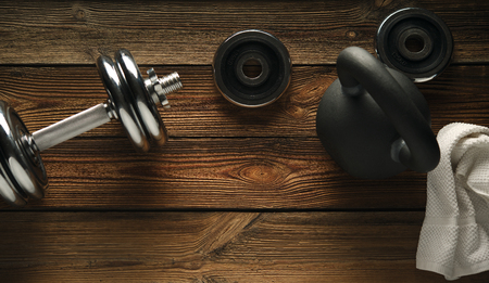 Top view of black iron kettlebell, dumbbell and white towel on wooden floor Sport background with copyspace  Weight lifting exercise concept. Standard-Bild