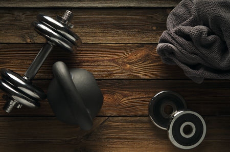 Top view of black iron kettlebell, dumbbell and grey towel on wooden floor Sport background with copyspace  Healthy diet and fitness concept