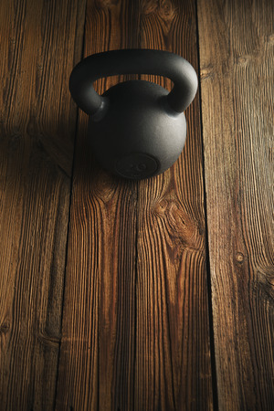 Top view of black iron kettlebell on wooden background Sport equipment background with copyspace Weight lifting exercise concept Stock Photo