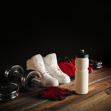 wood floor: Fitness equipment and supplements on wooden floor in gym Fitness background with Pair of Sneakers Water bottle Separate dumbbell plates and Red Gloves Perspective view with copy space
