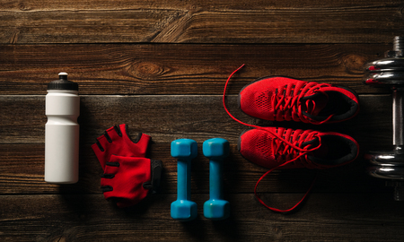 Top view Fitness equipment and supplements on wooden floor in gym Fitness background with Pair of Sneakers White water bottle Steel dumbbell and Pair of red gloves