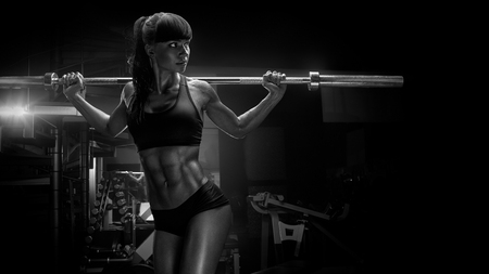 Black and white photo of fit young woman in great shape lifting barbells looking focused, working out in a gym. Sport, bodybuilding, lifestyle concept Sporty sexy woman doing squat workout Strong legs Wide 16 x 9 picture
