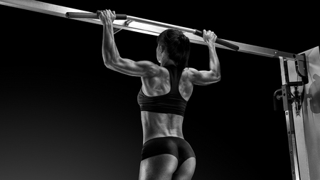 Black and white photo of professional Pull Up Workout Exercise Back Lats Muscles Pullups Pull torso up until the bar touches upper chest by drawing the shoulders and upper arms down and back. Stok Fotoğraf