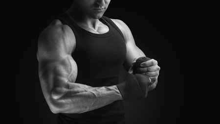 Close-up black and white photo of power athlete wrapping hands with boxing wraps isolated on black background Strong hands and fist, ready for training and active exercise