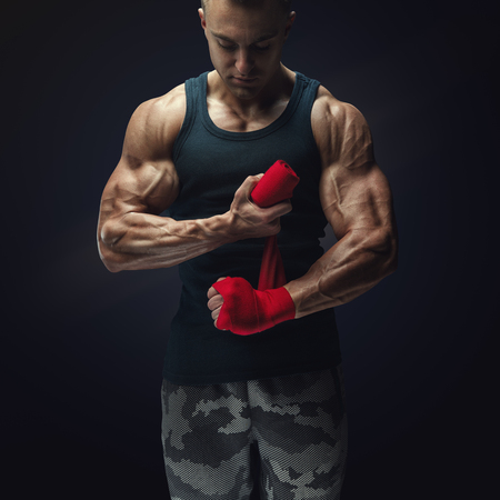 Strong man wrap hands on black background Man is wrapping hands with red boxing wraps isolated on black background Strong hands and fist, ready for training and active exercise photo