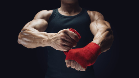 Close-up photo of strong man wrap hands on black background Man is wrapping hands with red boxing wraps isolated on black background Strong hands and fist, ready for training and active exercise photo