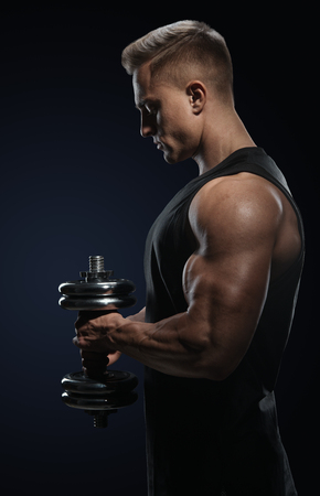 Handsome power athletic man in training pumping up muscles with dumbbell. Strong bodybuilder with perfect deltoid muscles, shoulders, biceps, triceps and chest. Close-up of a power fitness man. photo