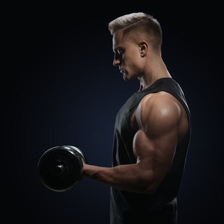 Athletic man in training pumping up muscles with dumbbell. Strong bodybuilder with perfect deltoid muscles, shoulders, biceps, triceps and chest. Close-up of a power fitness man. photo