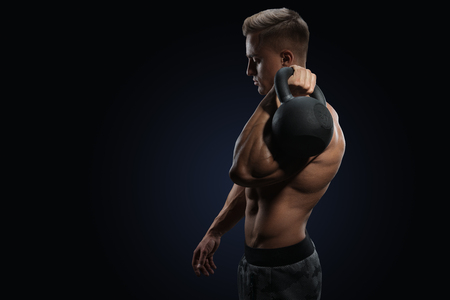 Young bodybulder holding a kettle bell Strong fitness male exercising crossfit with kettlebell in gym photo