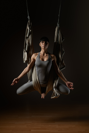 Portrait of beautiful woman taking lotus position and closing eyes while sitting in yoga hammock Young woman posing while doing anti-gravity aerial yoga in gray hammock on dark background photo