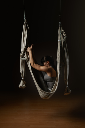 Personal trainer girl practicing aerial hammock yoga in studio Young woman posing while doing anti-gravity aerial yoga in gray hammock on dark background photo