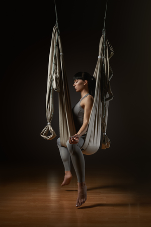 Silhouette of woman taking lotus namaste position and closing eyes while sitting in yoga hammock Young woman posing while doing anti-gravity aerial yoga in gray hammock on dark background photo