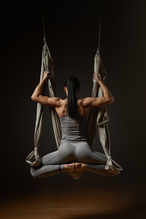 Back of young woman exercising aerial hammock yoga in studio Young woman posing while doing anti-gravity aerial yoga in gray hammock on dark background photo