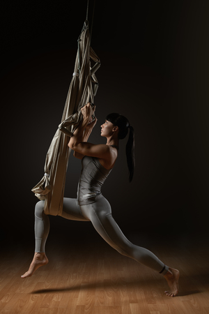 Young woman stretching by aerial hammock yoga in studio Young woman posing while doing anti-gravity aerial yoga in gray hammock on dark background photo