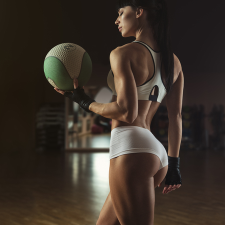 Beautiful pilates instructor holding a fitness ball turning back Fitness woman with toned body posing and holding fitness ball Young women exercising in aerobics class with medicine balls photo