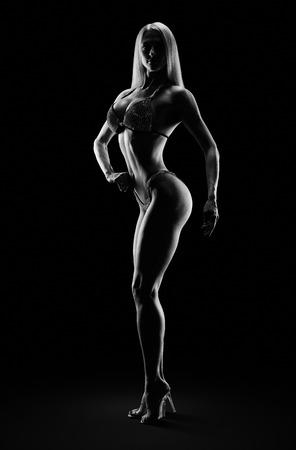 Fitness bikini model competition championship Attractive female athlete bodybuilder posing on stage Perfect trained body chest booty legs arms chest Black and white image Full size Clipping path Stock Photo