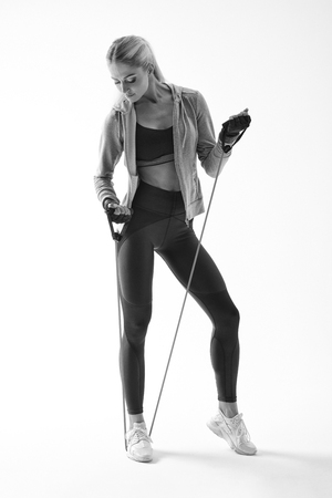 Black and white full length shot of fit young female fitness model Resistance band arms workout Attractive woman athlete in sportswear standing with resistance band on white background