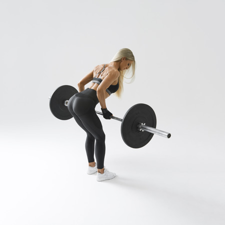 Full length photo of female bodybuilder doing crossfit training with barbell on white background Perfect trained body chest booty legs arms chest Copy space