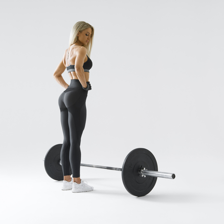 Woman with barbell in health club Female athlete before exercising with heavy weights at gym Bodybuilder performing deadlift exercise with weight bar Girl getting ready for crossfit training.