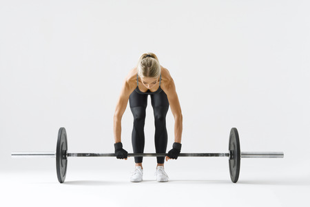 Fitness attractive woman preparing to practice deadlift with heavy weights Female bodybuilder doing heavy weight lifting work out on white background Horizontal picture